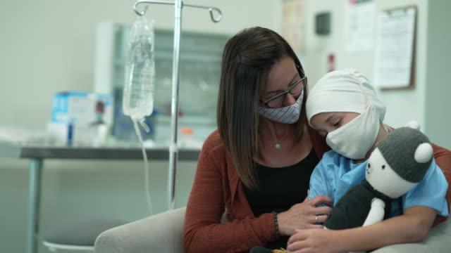 ヘッドスカーフとマスクを着用しながら、彼女のお母さんと一緒に座っている若い女性癌患者 - 白血病点の映像素材/bロール