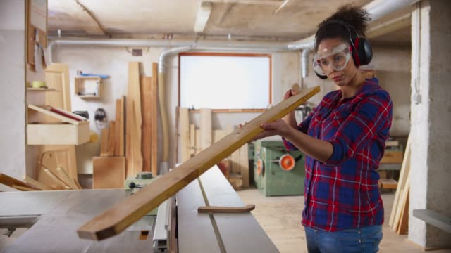 ld young female carpenter checking the plank she just cut on the table saw - skill stock videos & royalty-free footage