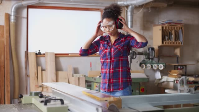 ds young female carpenter setting the table saw in the workshop - carpenter stock videos & royalty-free footage
