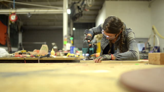 Young female carpenter working on wood