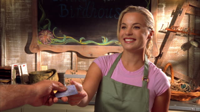 cu, young female cashier at garden center receiving credit card, cambria, california, usa - 金髪点の映像素材/bロール