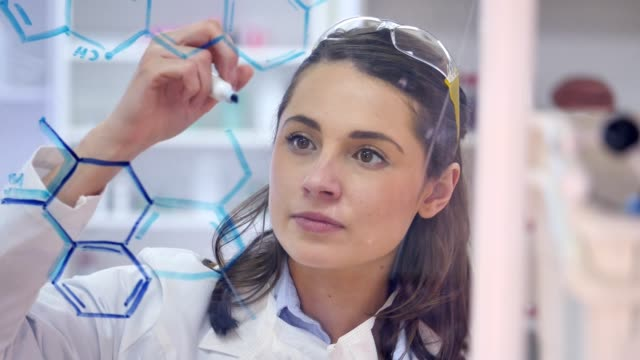 young female chemist confidently draws formula on transparent board - innovazione video stock e b–roll