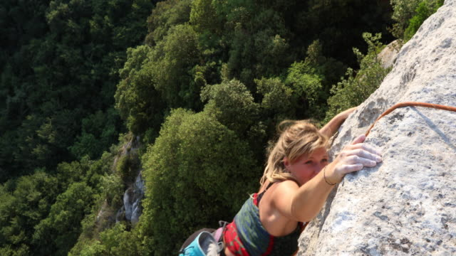 Young female climber ascends vertical rock, to belayer