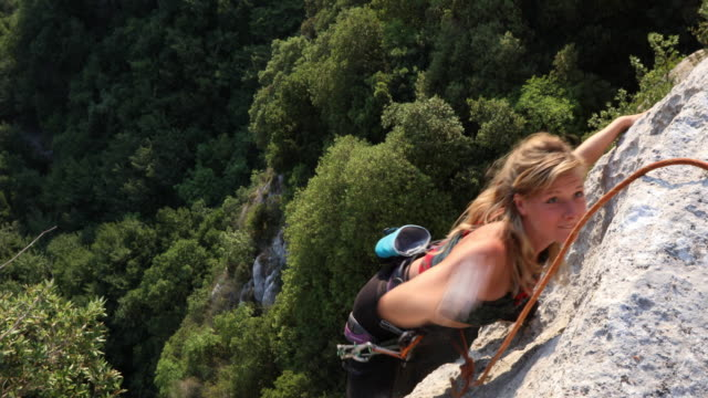 young female climber ascends vertical rock, to belayer - seil stock-videos und b-roll-filmmaterial