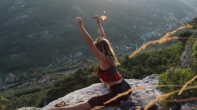 Young female climber stretches on summit of climb