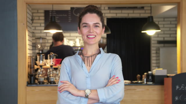 Young female coffee shop owner posing