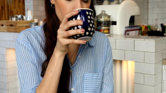 Junge Kundin Kaffeetrinken in Cafeteria