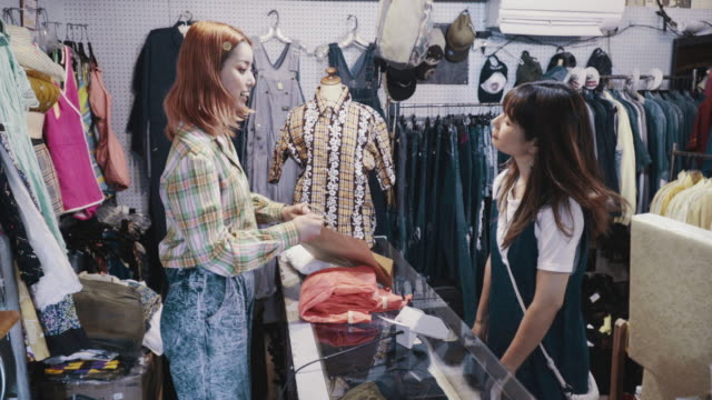 リサイクルショップでヴィンテージ衣料品を支払う若い女性顧客 - 衣料品店点の映像素材/bロール
