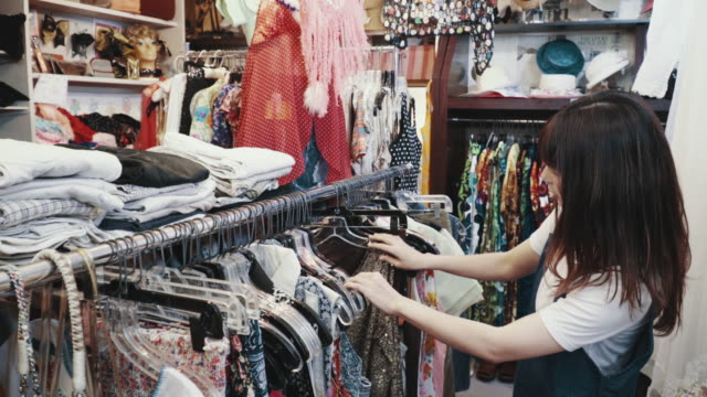 young female customer shopping for vintage clothing in a thrift store - second hand stock videos & royalty-free footage