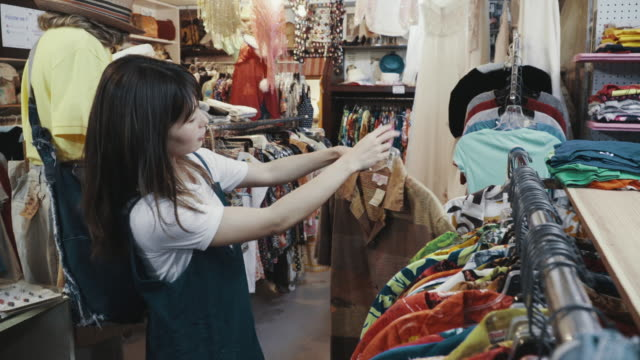 young female customer shopping for vintage clothing in a thrift store - garment stock videos & royalty-free footage