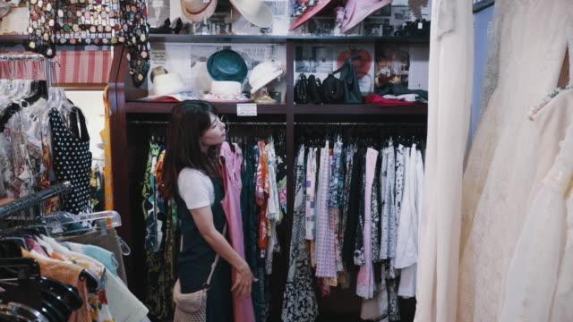 リサイクルショップでヴィンテージ衣料品を買う若い女性客 - 衣料品店点の映像素材/bロール