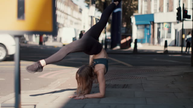 young female dancer exercising in the city - yoga stock videos & royalty-free footage