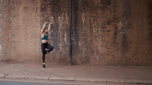 young female dancer jumping on sidewalk in front of brick wall - balance stock videos & royalty-free footage