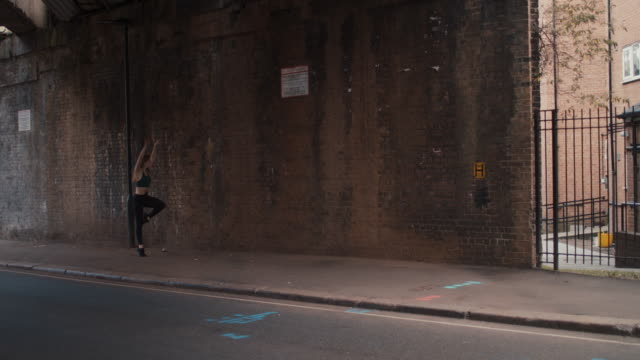 young female dancer jumping on sidewalk in front of brick wall - modern dancing stock videos & royalty-free footage