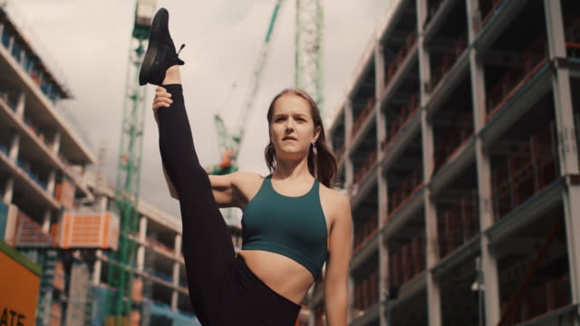 vídeos de stock, filmes e b-roll de young female dancer lifting one leg up in urban setting - evitar os outros