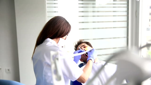 stockvideo's en b-roll-footage met jonge vrouwelijke tandarts werken - beschermende handschoen