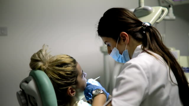 Young female dentist works in the office