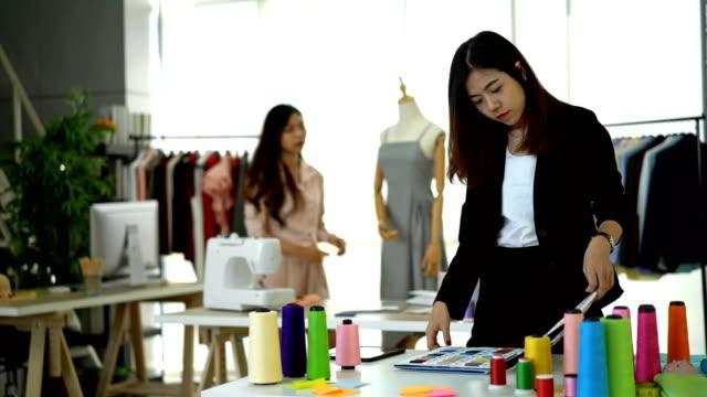 若い女性デザイナーは、バックグラウンドで彼女の同僚と顧客の要件を尋ねる - 生地サンプル点の映像素材/bロール