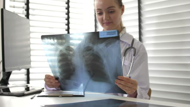 junge ärztin, die röntgenbild am schreibtisch im krankenhaus untersucht - wirbelsäule mensch stock-videos und b-roll-filmmaterial