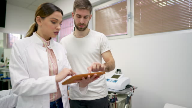 young female doctor explains to the patient his medical condition and proper therapy for it - physical therapist stock videos & royalty-free footage