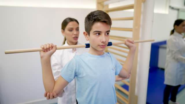 young female doctor helps young patient to use medical bar for shoulder exercise - rehabilitation center stock videos & royalty-free footage