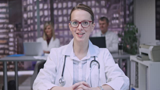 young female doctor on a video call from her office in the evening - one mature woman only stock videos & royalty-free footage