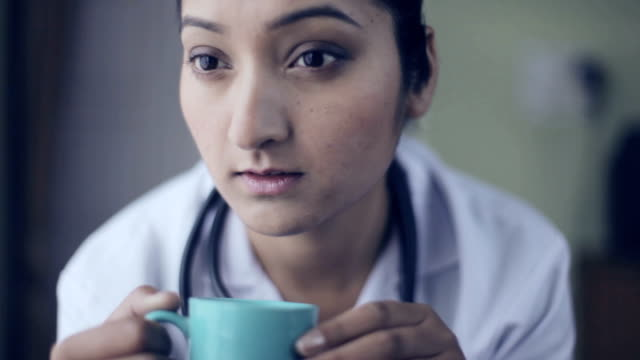 Young female doctor taking coffee break and looking through window.