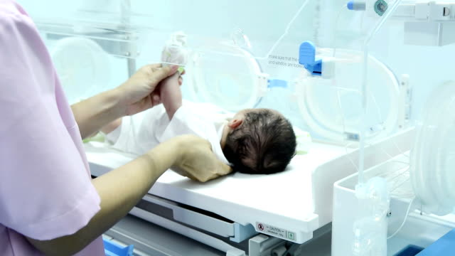 Young female doctor taking newborn baby off incubator