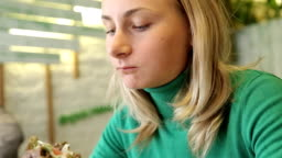 Young Female Eating Vegetarian Burger in Cafe