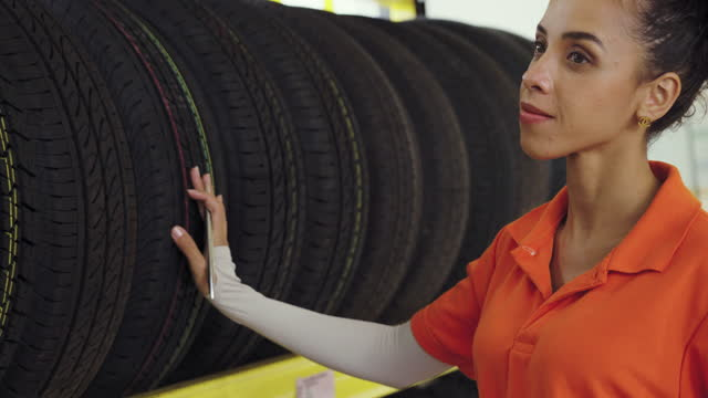young female employee checking the type of tires in the tire shop. - profile stock videos & royalty-free footage