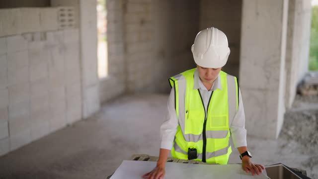 建設現場の青写真に取り組む若い女性エンジニア - 土木技師点の映像素材/bロール