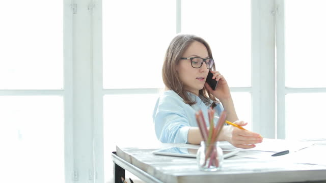 young female entrepreneur talking on the phone in her office. - moving activity stock videos & royalty-free footage