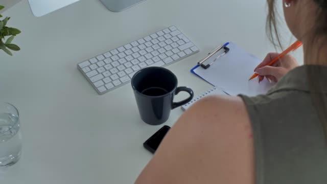 vídeos de stock, filmes e b-roll de jovem empreendedora escrevendo em seu bloco de notas enquanto trabalhava - note pad
