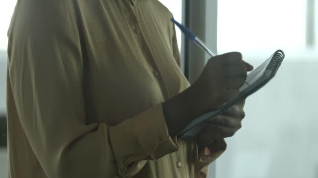 vídeos de stock, filmes e b-roll de young female entrepreneur writing in note pad - caneta