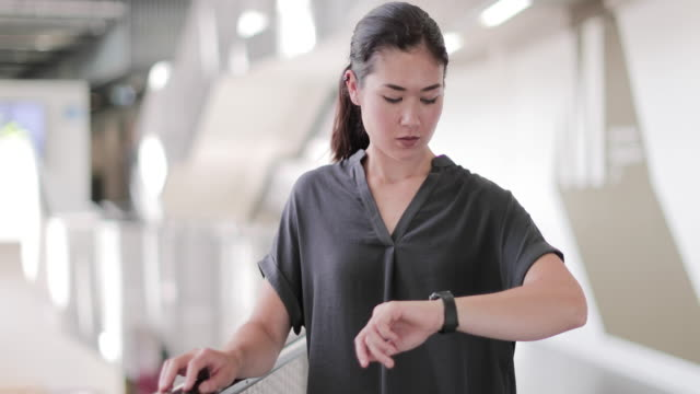 vidéos et rushes de young female executive using smartwatch - bureau pièce