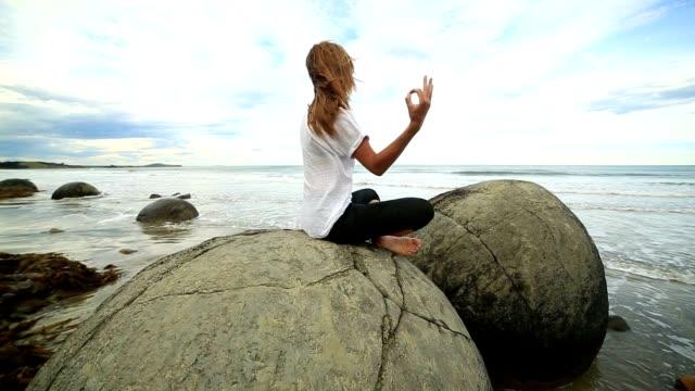 junge weibliche übungen yoga am strand - boulder rock stock-videos und b-roll-filmmaterial