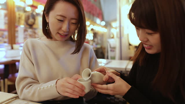 young female friends drinking 'saki' japanese rice wine in izakaya bar - japanese food stock videos & royalty-free footage