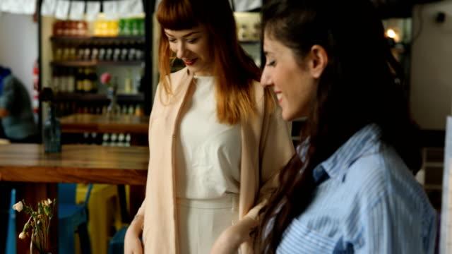 Junge weibliche Freunde Gruß vom Tisch im Cafe