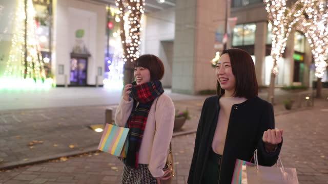 stockvideo's en b-roll-footage met jonge vrouwelijke vrienden die in stad bij nacht van kerstmis winkelen - deel 2 van 2 - cadeau