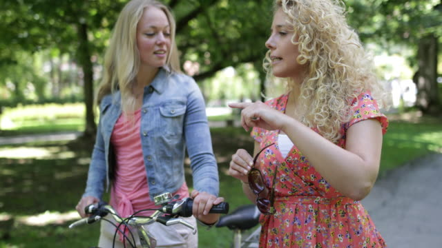 young female friends walking through a park together - einfaches leben stock-videos und b-roll-filmmaterial