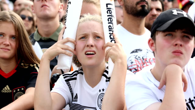 Young female German fan in football shirt is stunned and clutching his head while Germany is loosing the match of the FIFA World Cup Russia Group F...