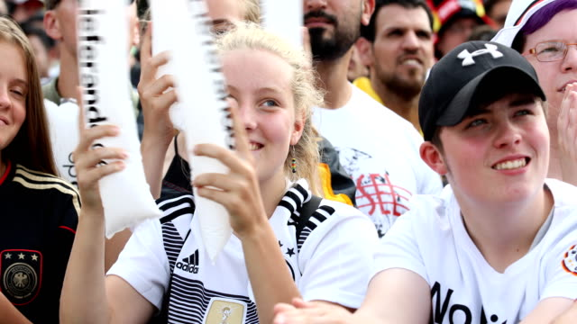 Young female German fans are singing hopeful 'Deutschland' 'Deutschland' and waving with plastic sticks while Germany is loosing the 2018 FIFA World...