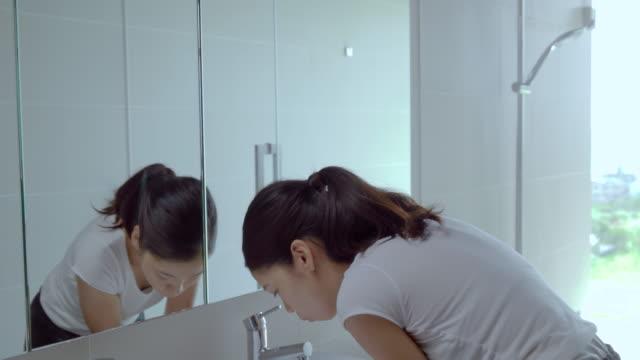 vídeos de stock, filmes e b-roll de jovem fêmea se preparando no banheiro. - escovar dentes