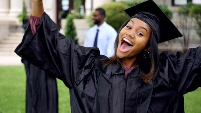 a young female graduate cheers while looking at the camera - females stock videos & royalty-free footage