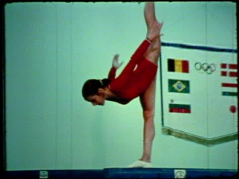 young female gymnast kyle gayner training on balance beam, performing flip & poses, gymnast performing on balance beam during competition, judges... - akrobat bildbanksvideor och videomaterial från bakom kulisserna