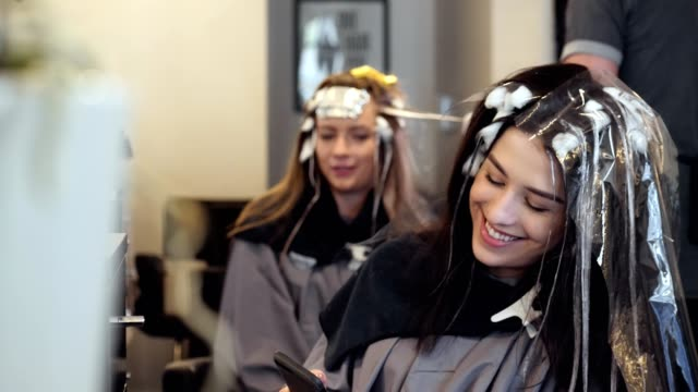 young female hair salon customer uses smartphone as she waits for new hair color to set - highlights hair stock videos & royalty-free footage