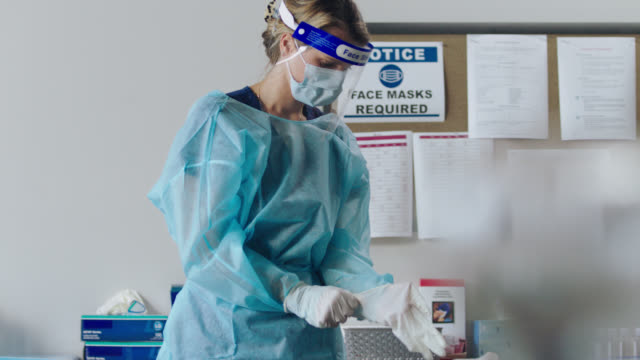 young female healthcare professional puts on personal protective equipment before sitting down to write on clipboard in medical clinic - medical occupation stock videos & royalty-free footage