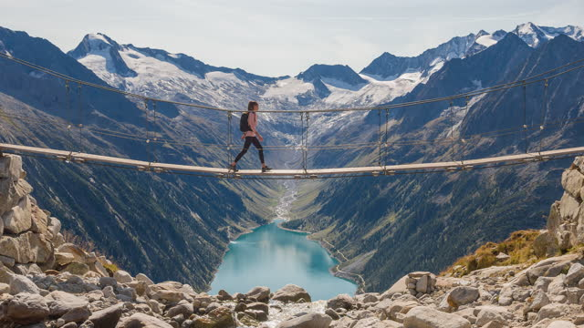 stockvideo's en b-roll-footage met jonge vrouwelijke wandelaar die een hangende brug over zoet waterstroom hoog in de bergen kruist, die van majestic mening van het meer van de bergvallei geniet - brug mens gemaakte bouwwerken