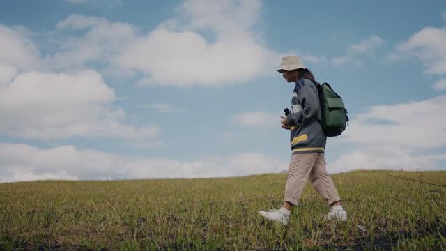 草の風景の上を歩く若い女性ハイカー - 双眼鏡点の映像素材/bロール