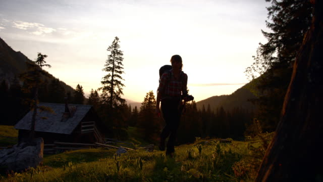 young female hiker walking towards camera from a wooden cabin at sunset - cabin stock videos & royalty-free footage
